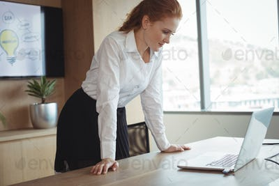 Young businesswoman looking at laptop while leaning on desk