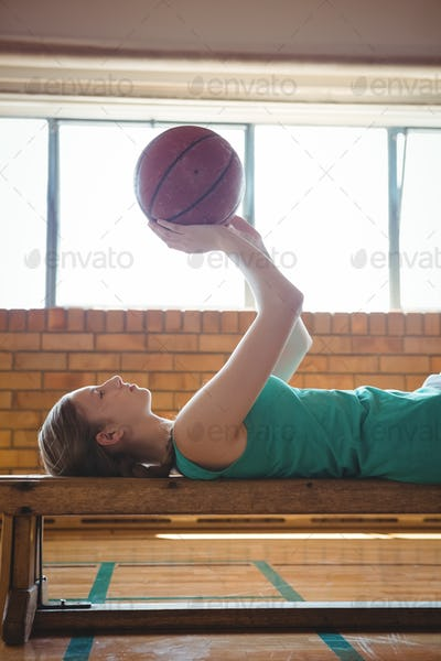 Female player playing with basketball while lying on bench in court