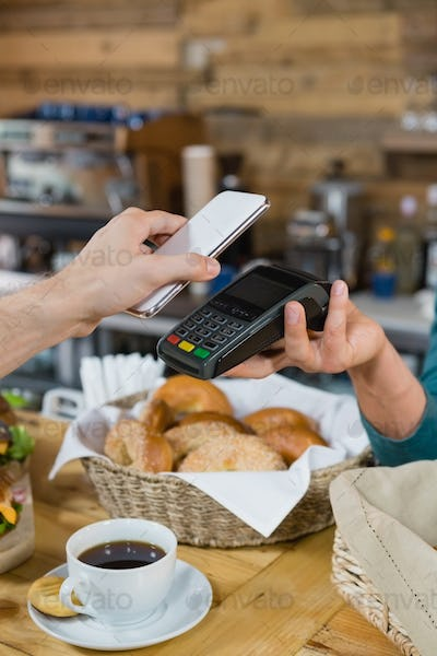 Customer paying bill through smartphone using NFC technology at counter
