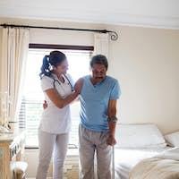 Female doctor helping senior man to walk with walker in bedroom