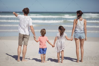 Man pointing away while standing with family at beach