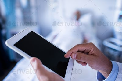 Hands of male doctor using digital tablet