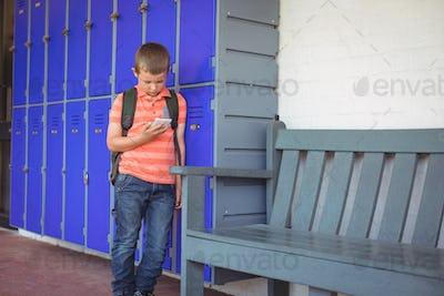 Boy using mobile phone while leaning on lockers