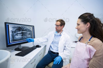 Dentist showing an x-ray of teeth to female patient
