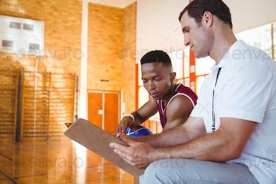 Coach explaining to basketball player