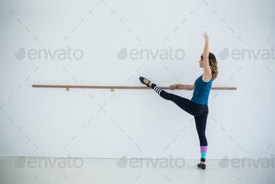 Dancer stretching on a barre while practicing dance