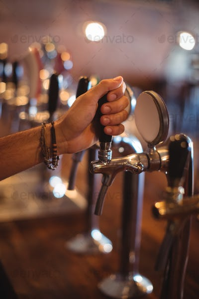 Bartender hands using beer tap in pub