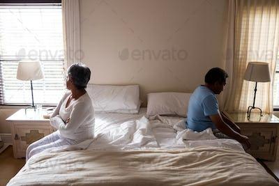 Upset senior couple ignoring each other in bedroom