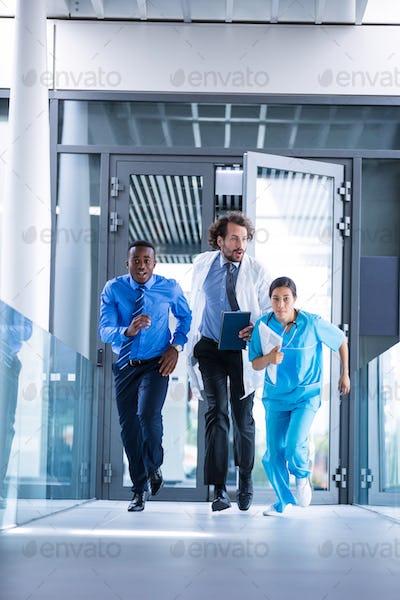 Businessman, doctor and nurse in hospital corridor