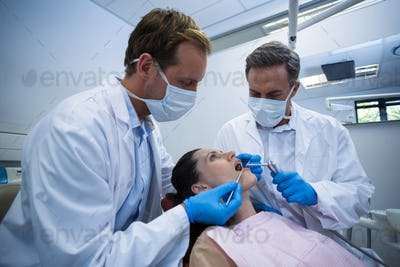 Dentists examining a female patient with tools