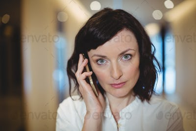 Portrait of female executive talking on mobile phone in corridor