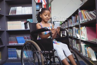 Girl using digital tablet on wheelchair in library