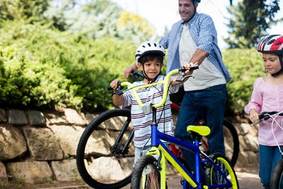 Father and children standing with bicycle in park