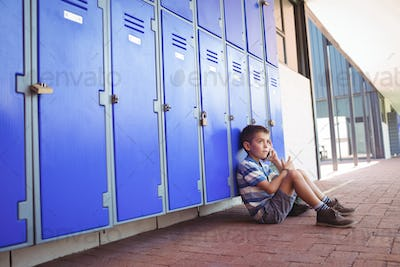 Side view of boy talking on mobile phone while sitting by lockers