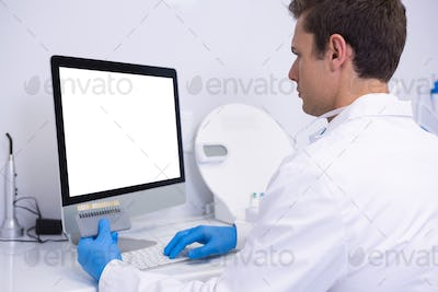 Dentist working on computer against wall