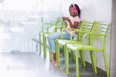 Girl listening to music from digital tablet