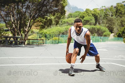 Full length of male teenager practicing basketball
