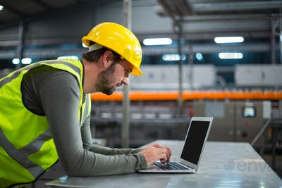 Factory worker using laptop