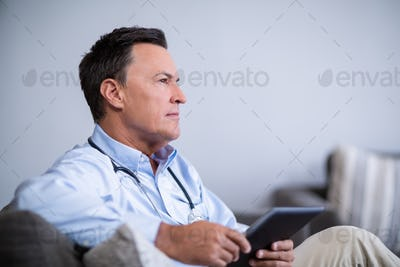 Thoughtful doctor holding digital tablet