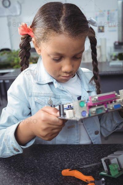 Focused elementary student examining circuit board