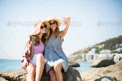 Female friends taking selfie while sitting on rock