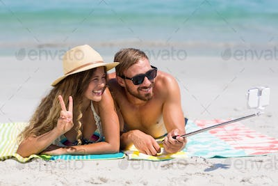 Couple taking selfie with monopod while lying at beach