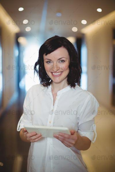Portrait of female executive holding digital tablet