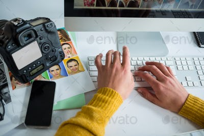 Male photographer working over computer at desk