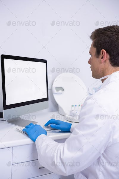 Side view of dentist working on computer
