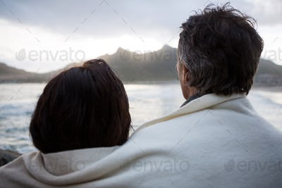 Rear view of couple wrapped in shawl on beach