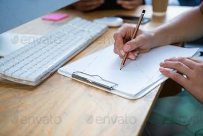 Close-up of female business executive writing on clipboard at desk