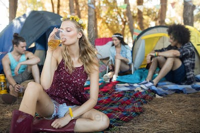 Young woman drinking beer while sitting at campsite