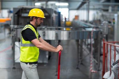 Factory worker pulling trolley in factory