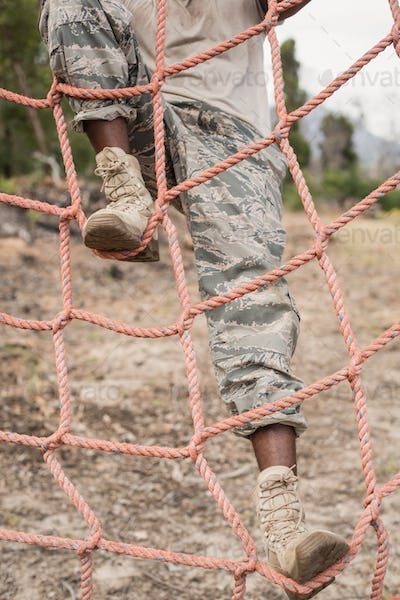 Military soldier climbing a net during obstacle course