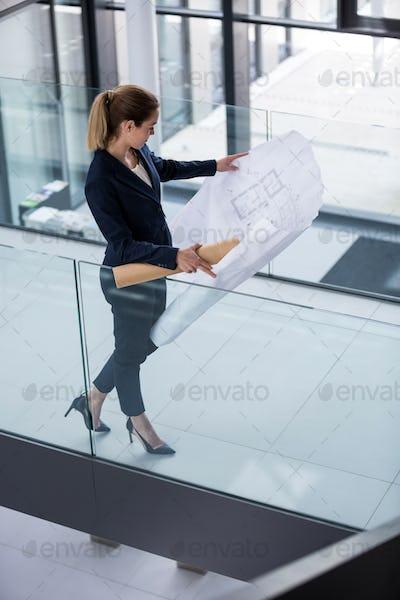 Businesswoman standing at corridor with blueprint