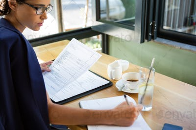 Female executive writing in diary at cafe