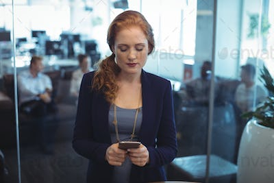 Young businesswoman using mobile phone at office