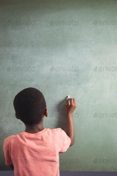 Boy writing with chalk on greenboard