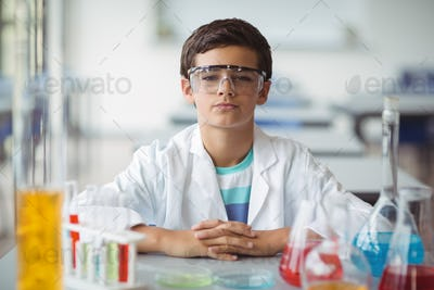Portrait of schoolboy sitting in laboratory