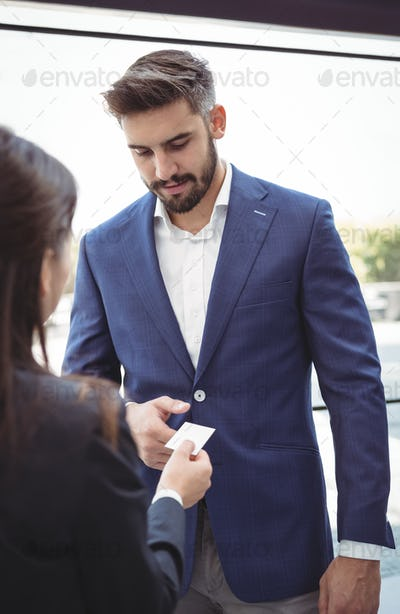 Businesswoman giving visiting card to businessman