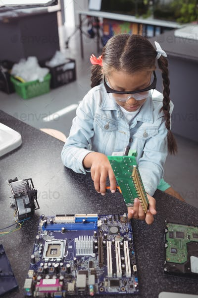 Elementary girl assembling circuit board on desk