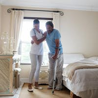 Female doctor helping senior man to walk with crutches in bedroom