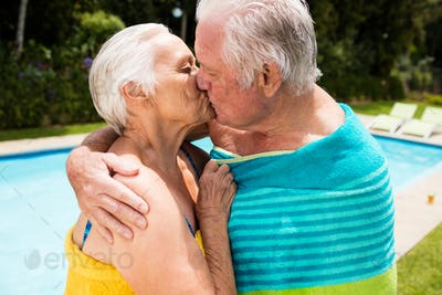 Senior couple kissing each other at poolside