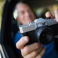 Man photographing with camera in car