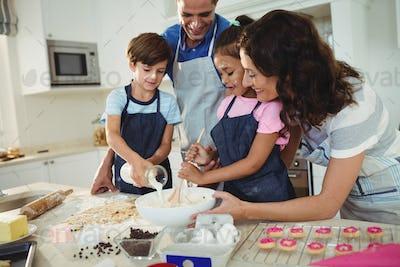 Happy family preparing cookies in kitchen