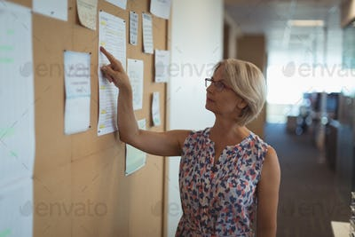 Businesswoman reading paper on notice board