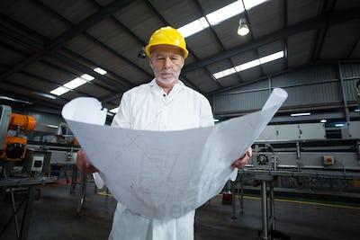 Factory engineer looking at blueprint