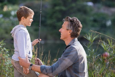 Smiling father and son holding fishing rod