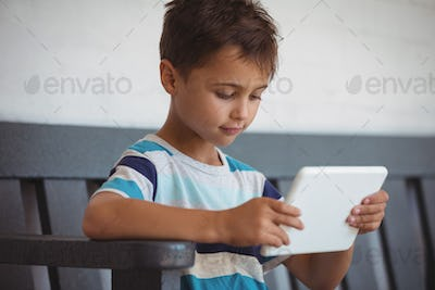 Boy using digital tablet while sitting on bench