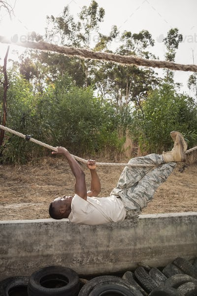 Young military soldier practicing rope climbing during obstacle course